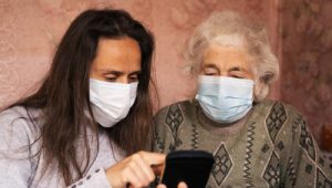 2 women wearing masks looking at mobile device