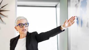 woman gesturing towards whiteboard